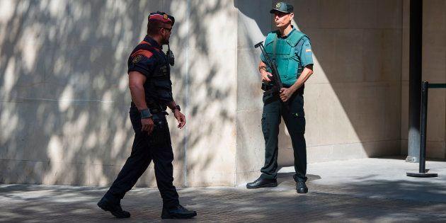 Un mosso d'esquadra pasa ante un guardia
