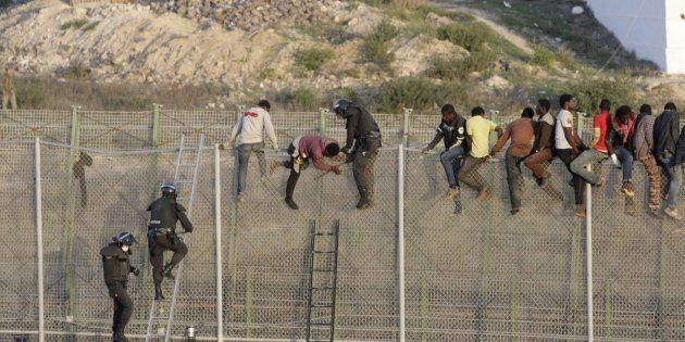 Agentes de policía tratan de impedir que un grupo de subsaharianos salte la valla entre Melilla y Marruecos,...