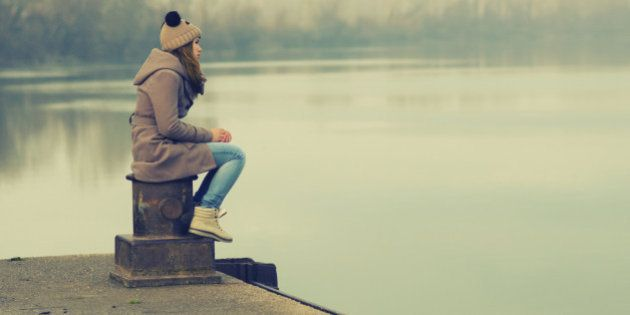 Lonely teenage girl sitting on the dock on cold winter