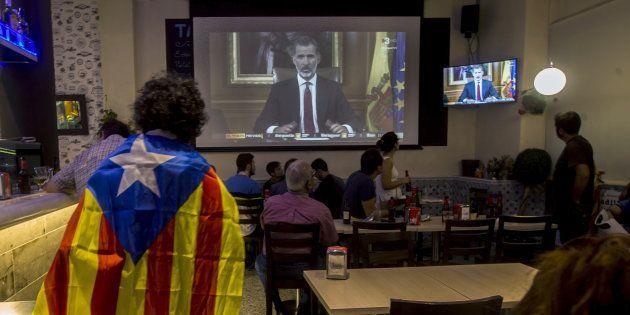 Varias personas miran el discurso del Rey Felipe