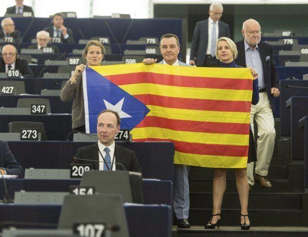 Eurodiputados posan con una bandera estelada durante el debate en el Parlamento