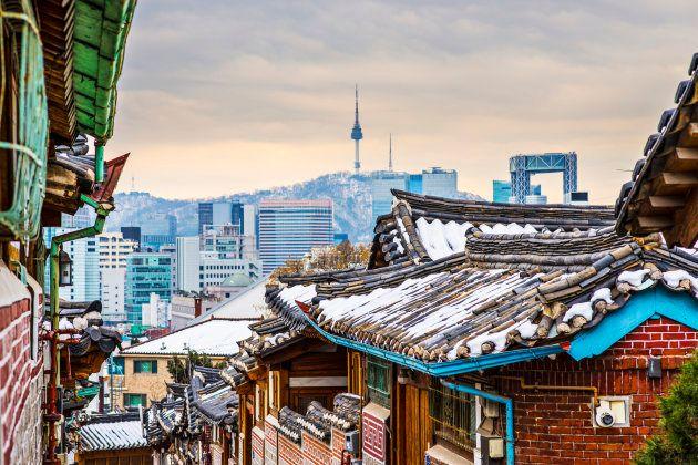 Imagen de dos zonas de Seúl, el barrio histórico de Bukchon Hanok y, al fondo, la ciudad