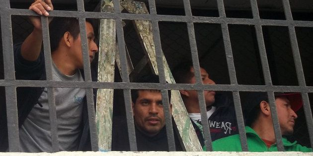 Varios presos miran por una ventana de la cárcel de Lurigancho, al este de Lima. El complejo, de 20 pabellones,...