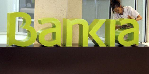 Una operaria limpia el logo de Bankia en la sede central de