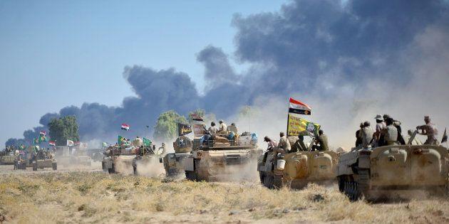 Fuerzas chiítas y soldados de Irak accediendo, ayer, a Al