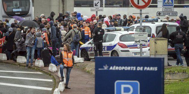Un grupo de pasajeros, evacuados del aeropuerto de Orly, congregados en los alrededores a la espera de