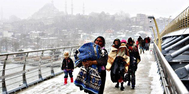 Refugiados sirios caminan hacia una estación de Estambul, buscando