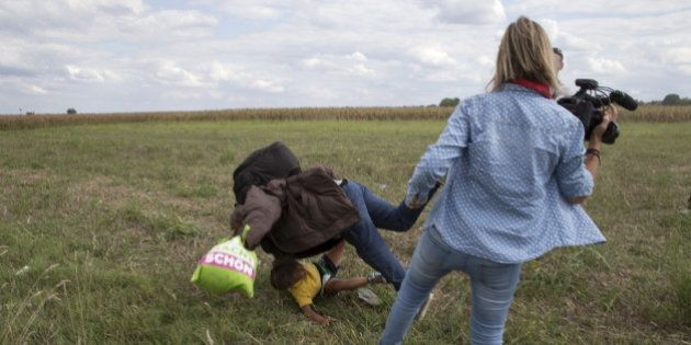 A migrant carrying a child falls after tripping on TV camerawoman (R) Petra Laszlo while trying to escape...