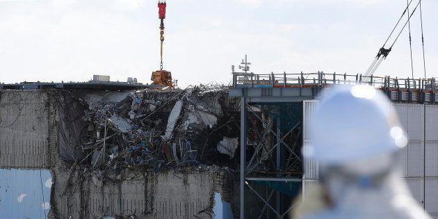 Un periodista se cubre la cara ante el reactor 3 de la central