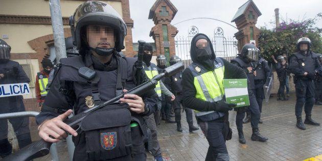 Agentes antidisturbios de la Policía Nacional retiran material electoral de un instituto de L'Hospitalet...