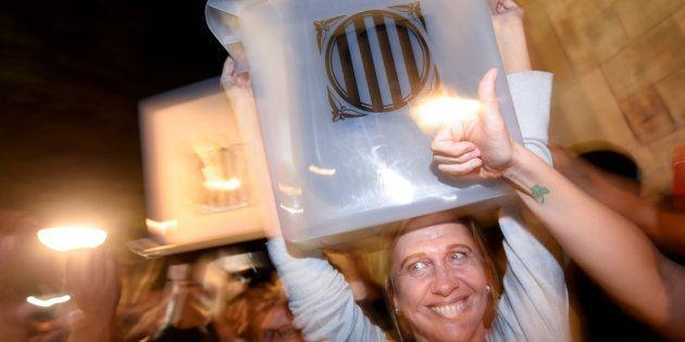 Una mujer sostiene feliz una de las urnas usadas en el referéndum del pasado 1 de octubre, en