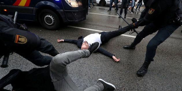 Agentes de la Policía Nacional arrastran a varios de los concentrados en un colegio electoral de Barcelona,...