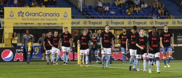 Los jugadores de Las Palmas y del Celta de Vigo saltan al campo con una camiseta negra con el lema
