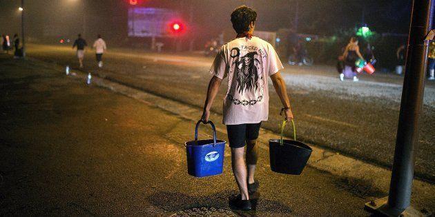Un hombre porta dos cubos de agua para ayudar a sofocar uno de los focos declarados en el centro de la...