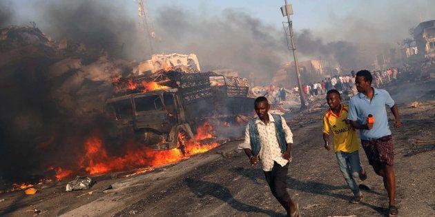Un grupo de ciudadanos y de reporteros, evacuados de la zona del atentado, donde aún arde uno de los...