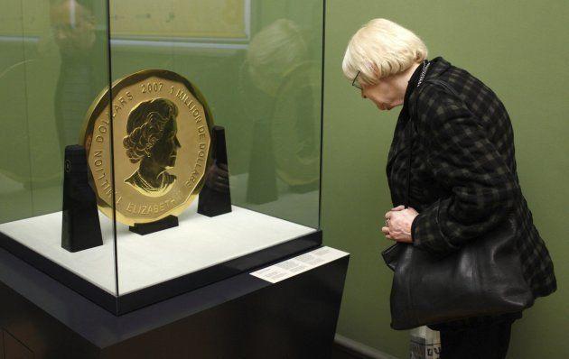 Fotografía de archivo tomada el 8 de diciembre de 2010 que muestra a una mujer que observa una moneda...