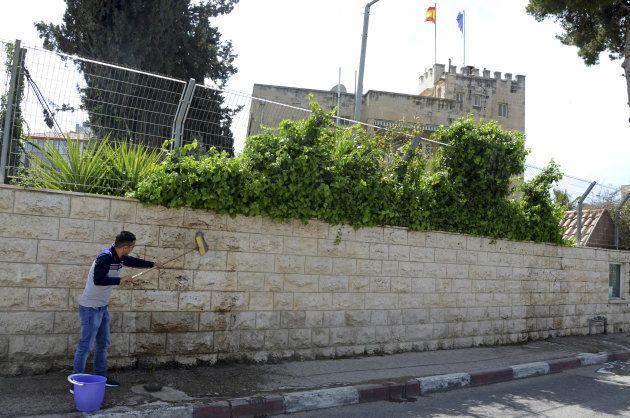 Un trabajador del Consulado de España en Jerusalén limpia la pared, tras el ataque vandálico del domingo...