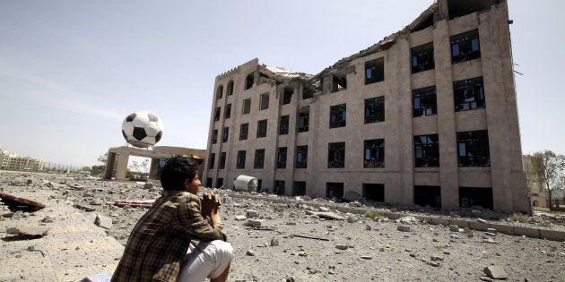 Un joven juega ante la antigua sede de la Federación de Fútbol de Yemen, dañada por un bombardeo de Arabia...