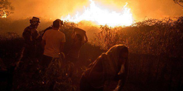 Unos vecinos observan cómo se acerca a sus casas el incendio forestal de Carballeda de Avia