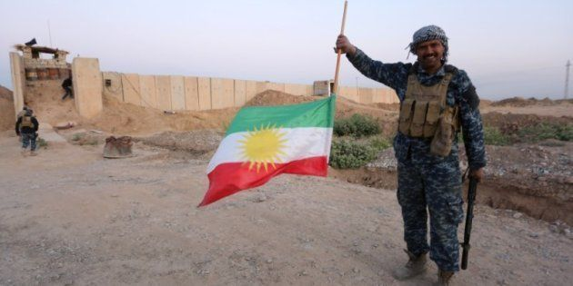 Un soldado iraquí sostiene dada la vuelta la bandera del Kurdistán, esta mañana en