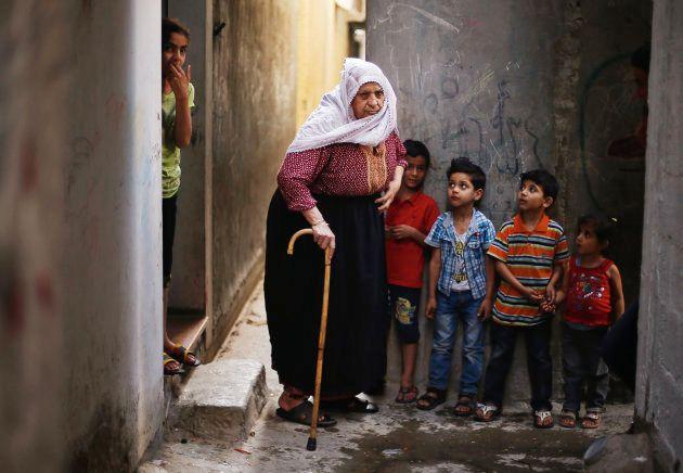 Una anciana y un grupo de niños, en el campo de refugiados de Jabalia,