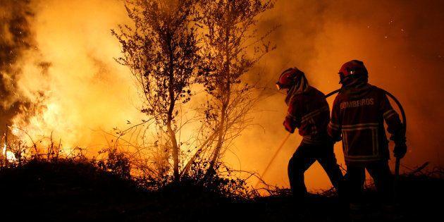 Una pareja de bomberos trata de apagar las llamas en el foco de Cabanoes, cerca de Lousa, Portugal, el...