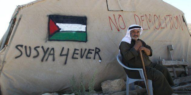 Un palestino descansa ante su tienda en la villa de Susya, Cisjordania, amenazada por demoliciones en