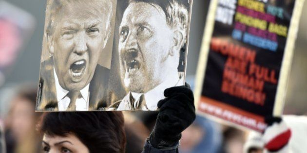 A participant of a Women's March in Helsinki holds up a poster depicting US President Donald Trump and...
