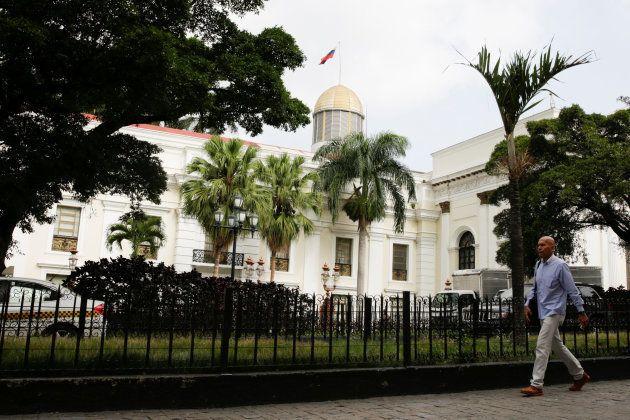 Un hombre camina ante la sede de la Asamblea Nacional venezolana, en