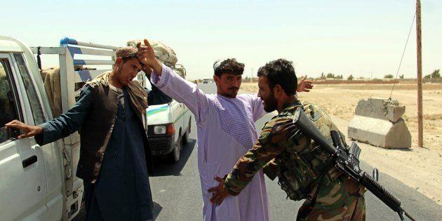 Un soldado registra a un ciudadano en un control en el distrito de Maiwind, en Kandahar (Afganistán),...