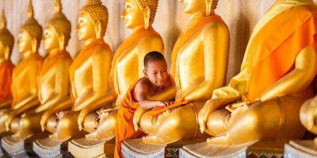 Young novice monk scrubbing buddha statue at old temple in