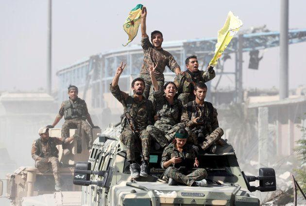 Miembros de las Fuerzas Democráticas de Siria, paseando triunfantes el pasado miércoles por las calles...