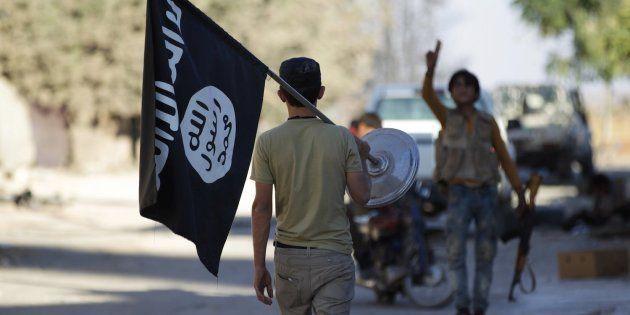 Un rebelde toma la bandera del ISIS después de que los yihadistas escapasen de la localidad de Akhtarin,...