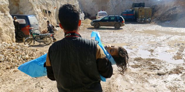 Un fotógrafo traslada a una niña afectada por el supuesto ataque con armas químicas en Jan Sheijun, Siria,...