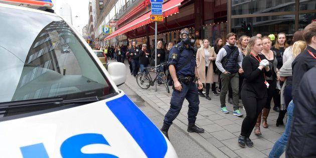 Miembros de la policía sueca con máscaras antigas evacuan las calles contiguas a la zona donde un camión...