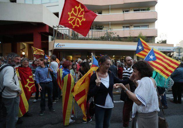 Personas sostienen banderas catalanas y gritan consignas durante una manifestación frente al consulado...