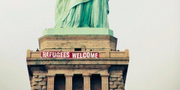 Activistas colocan una pancarta de apoyo a los refugiados en la Estatua de la
