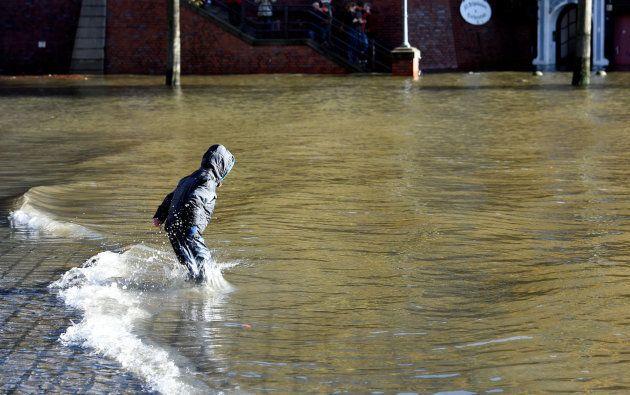 Un niño juega con el agua en las calles de