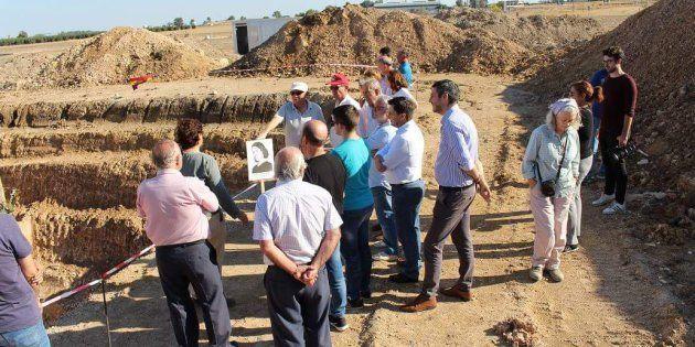Un grupo de visitantes, ante la tierra abierta durante la excavación, en el cortijo de El