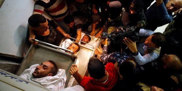 Familiares, amigos y personal cercano a la Yihad Islámica, junto a los cuerpos de tres de los fallecidos,...