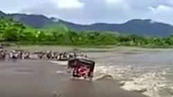 Un autobús con pasajeros, arrastrado por la corriente en un río de