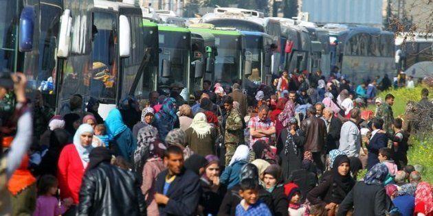 Sirios evacuados de Kefraya y Fua se organizan para subir a los autobuses, una vez restablecido el