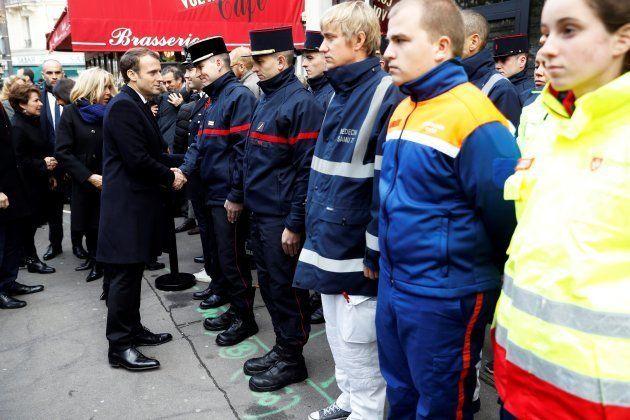 Emmanuel Macron y su esposa Brigitte saludan a miembros de los servicios de emergencia que actuaron el...
