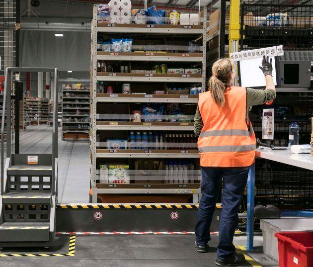 Una trabajadora prepara un pedido con ayuda de los robots de Amazon (naranjas, bajo las estanterías)...