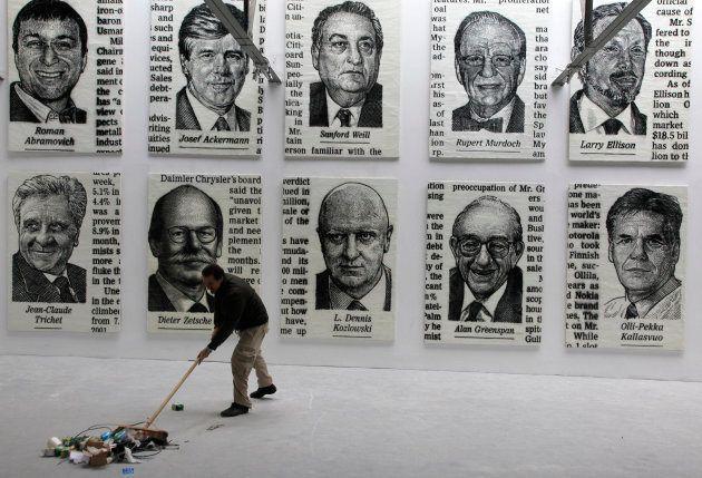El artista José María Cano barre la basura frente a sus retratos de líderes expuestos en una galería...