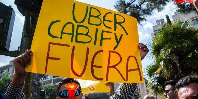 Un taxista se manifiesta en Madrid en contra de los servicios de transporte Uber y Cabify. Marcos del...
