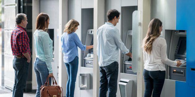 Un grupo de clientes retiran dinero en cajeros