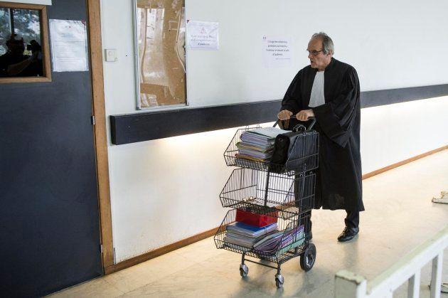 Un abogado lleva, ayudado por un carrito, la documentación legal del proceso del proceso de la familia...