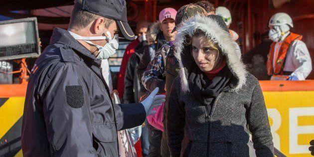 Un agente de la Policía Nacional ayuda a una inmigrante embarazada a desembarcar del buque de salvamento...
