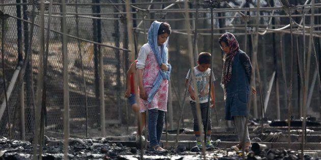 Unos niños pasean entre los restos del campamento de Moria (Lesbos, Grecia), arrasado parcialmente por...